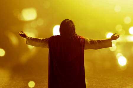 Rear view of Jesus Christ raised hands and praying to god with blurred light background