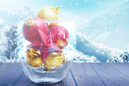 Colorful Christmas ornament in the glass bowl on wooden table with snowfall background Archivio Fotografico