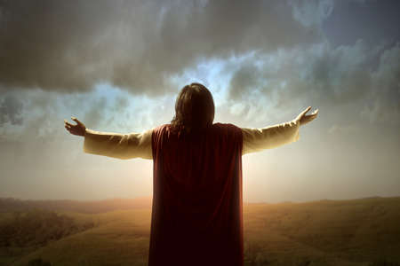 Rear view of Jesus Christ raised hands and praying to god with a sunrise sky background Archivio Fotografico