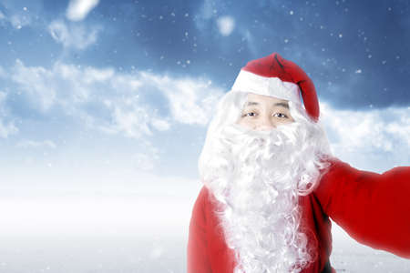 Asian man in Santa costume taking a selfie with a snowfall background. Merry Christmas Archivio Fotografico