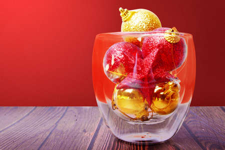 Colorful Christmas ornament in the glass bowl on wooden table with a colored background