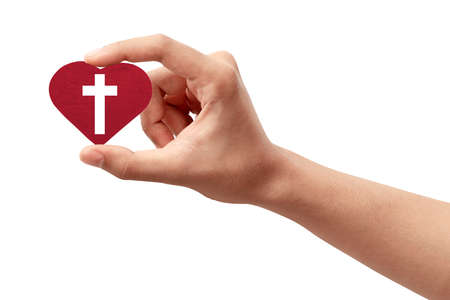 Human hand holding a red heart with a Christian cross isolated over white background Archivio Fotografico