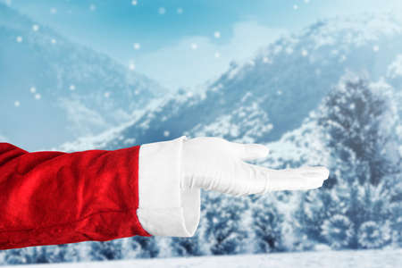 Santa Claus with an open hand gesture with snowfall background. Empty space for copy space
