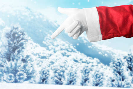 Santa Claus hand pointing something with snowfall background. Empty space for copy space