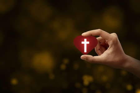 Human hand holding a red heart with a Christian cross with blurred light background