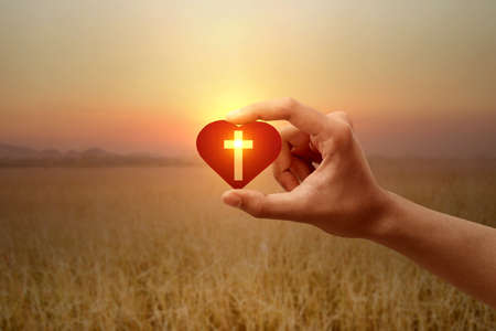Human hand holding a red heart with a Christian cross with a sunrise sky background