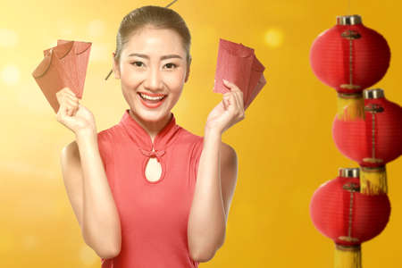 Asian Chinese woman in a cheongsam dress holding red envelopes. Happy Chinese New Year