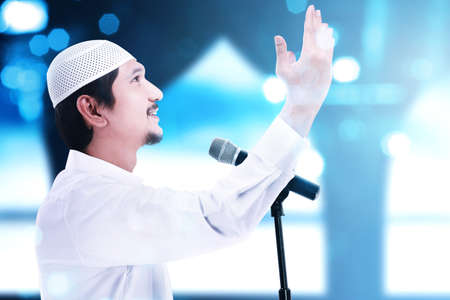 Asian Muslim man standing while raised hands and giving a sermon with blurred light background