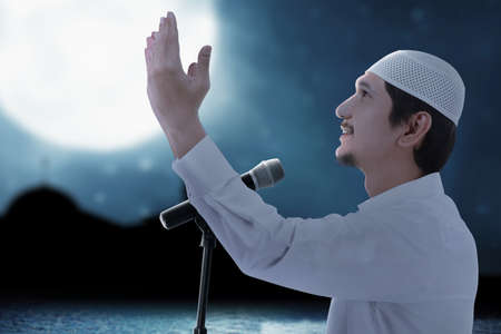 Asian Muslim man standing while raised hands and giving a sermon with the night scene background