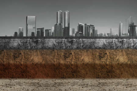 Underground soil layer of cross-section earth with concrete on the top with cityscapes background