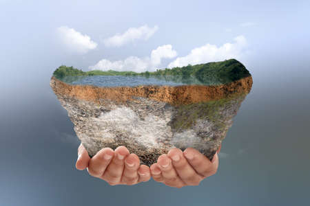 Human hand holding underground soil layer of cross-section earth with lake and hills on the top with colored background
