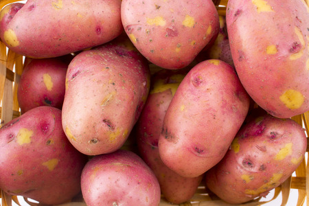 Fresh potatoes in basket isolated on white background photo