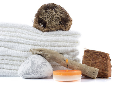 spa decoration with stones, wooden items, candle and white towels on a white background with clipping path photo