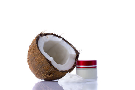 Shredded coconut and box with cream on white background photo