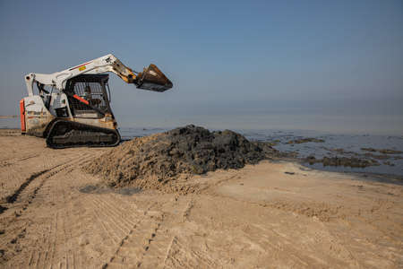 Skid steer loader or bobcat, works to clean the beach Editorial