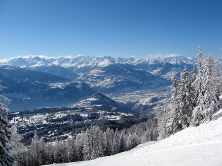valais: Scenic view of ski slopes in resort of crans montana with mountains in background, valais, switzerland.