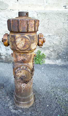 source of iron: detail of Rusty hydrant on blurred grey background Stock Photo
