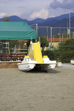 sunbath: detail of yellow pedalo on the beach in italy Stock Photo