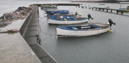 detail of fishing boat in a harbour during rain