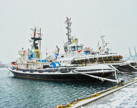 tug boat covered by snow in italy Editorial