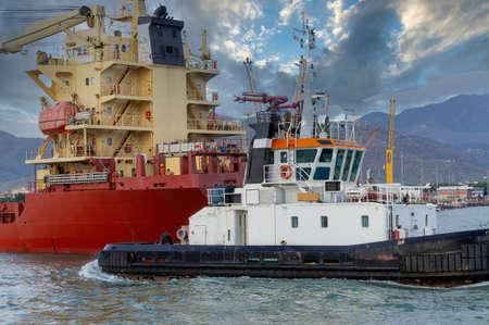tug boat enter with a ship in marina di carrara harbour Foto de archivo