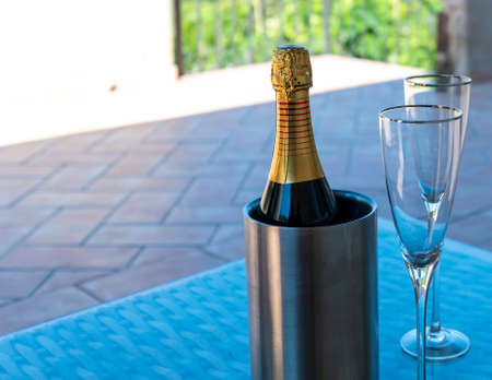 one bottle of champagne with two glass on top a table