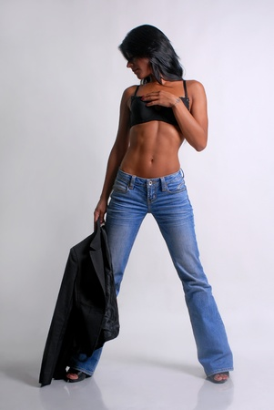 A woman dressed with a jeans on grey background photo