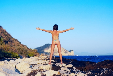Happy woman in thong on the beach photo