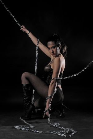 Sexy woman with heels and chains looking you