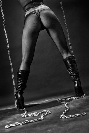 Sexy woman with heels and chains from back