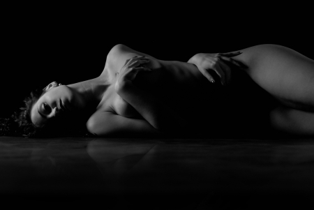 Fine art nude woman on black background Stock Photo