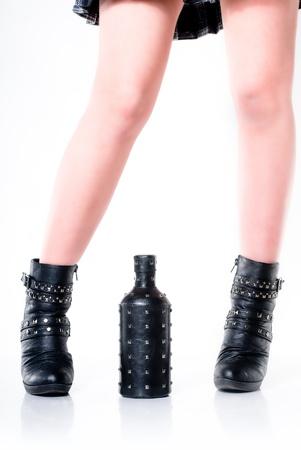 Dark feet with a dark bottle on white background photo