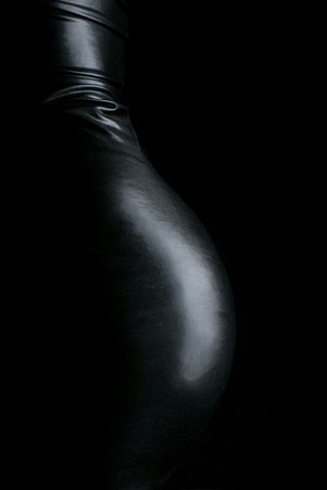 Profile of a butt with a blacl leader skirt on black background Stock Photo
