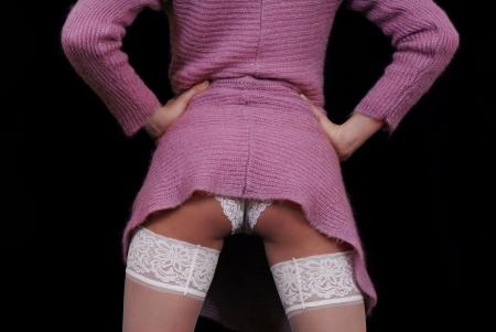 mini skirt: Culo atractivo con medias blancas y pantie en bacground negro Foto de archivo