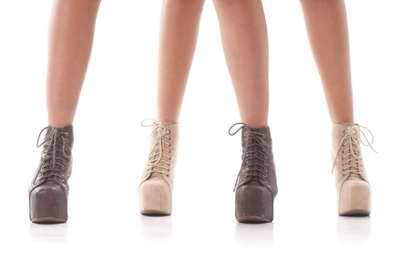 Two isolated pair of woman legs with fashion shoes on white background