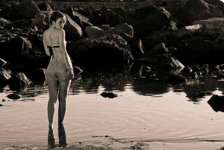 Vintage girl walking in the water looking you photo