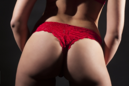 Beautiful ass with red lingerie on dark background Stock Photo