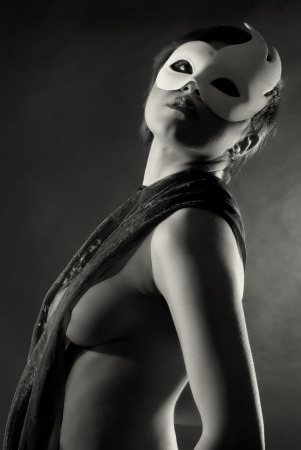 Sexy naked woman with white carnival mask in black and white photo