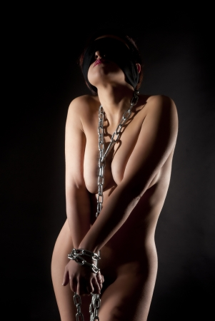 One blindfolded naked woman with chains on black background