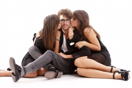 Two young attractive women kissing an happy man on white background
