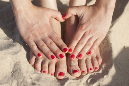 Foot and hands on the sand with red nails
