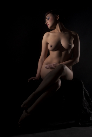 Sad naked woman sit isolated on black background