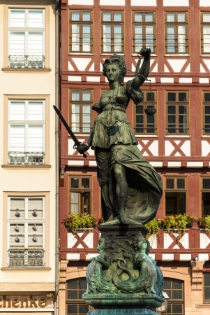 justice statue: Frontal view of the Justice statue in Frankfurt with ancient palaces in background