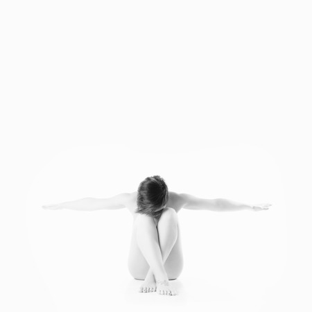 Isolated black and white naked woman sit on white background photo
