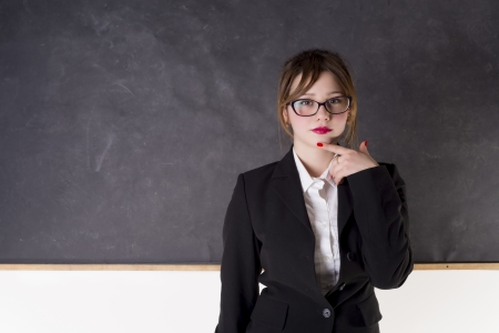 Sexy teacher with blackboard looking you photo