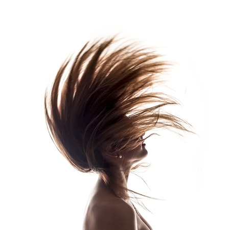 Isolated woman portrait side view in back light with hair in the wind Stock Photo