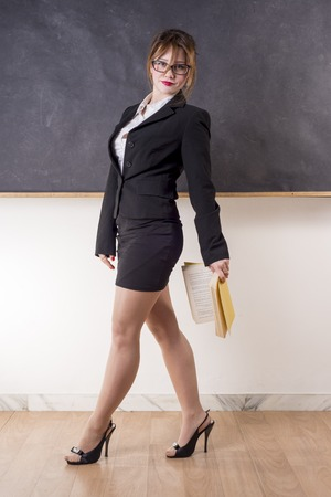 Sexy teacher with blackboard looking you with a book photo