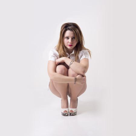 jeune fille adolescente nue: Isol� femme sexy triste assis seul dans un fond gris