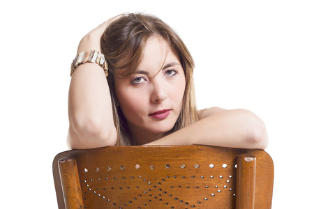 Beautiful Woman Leaning On Wooden Chair Over White Background photo