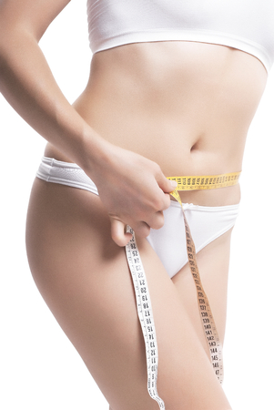 Closeup Of Woman Measuring Her Waistline With Measurement Tape